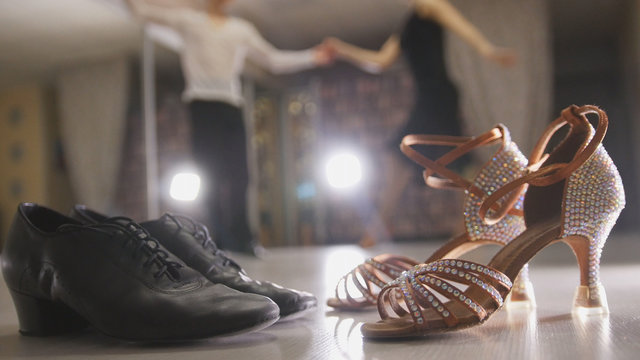 Blurred professional man and woman dancing Latin dance in costumes in studio, two pairs ballroom shoes in the foreground
