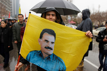 A Kurdish demonstrator holds a flag during a protest demanding the release of the Kurdistan Workers Party (PKK) leader Abdullah Ocalan, in Sulaimaniyah