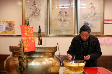 A man lights incense to welcome in the Chinese Lunar New Year of the Dog in Manhattan's Chinatown in New York