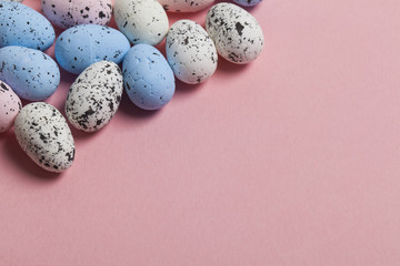 A collection of easter eggs on a pastel pink background