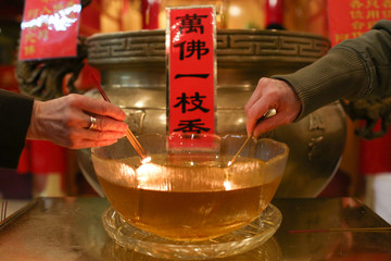 People light incense to bring in the Chinese Lunar New Year of the Dog at Mahayana Buddhist Temple in New York