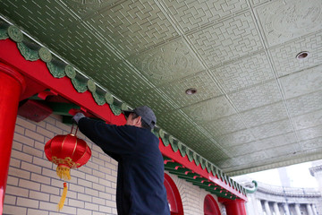 A man hangs a lantern for the Chinese Lunar New Year at Mahayana Buddhist Temple in Manhattan, in New York