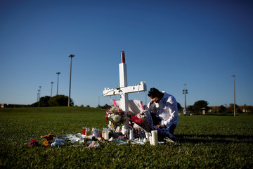 Joe Zevuloni mourns in front of a cross placed in a park to commemorate the victims of the shooting at Marjory Stoneman Douglas High School, in Parkland