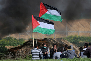 Palestinian demonstrators take cover during clashes with Israeli troops, near the border with Israel in the southern Gaza Strip