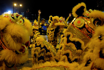 A girl dressed as a jockey is seen among lion dancers during a parade to celebrate the Year of the Dog in Hong Kong