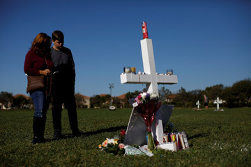 People mourn in front of a cross in a park where crosses were placed to commemorate the victims of the shooting at Marjory Stoneman Douglas High School, in Parkland