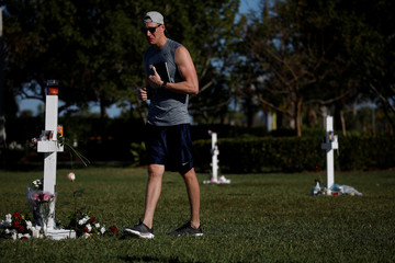 A man mourns in a park where crosses were placed to commemorate the victims of the shooting at Marjory Stoneman Douglas High School, in Parkland