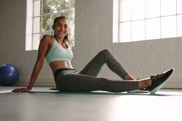 Smiling fitness woman resting on exercising mat