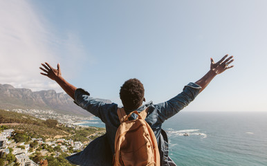 Man enjoying the view from top of mountain Wall mural