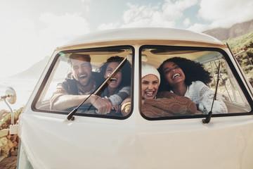 Friends on roadtrip sitting inside van