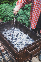 man rakes coals in brazier with metal poker