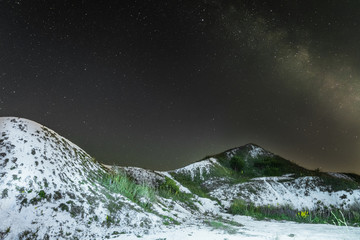 Starry night sky with milky way over the white cretaceous hills. Night natural landscape with chalk ridges. Natural archaeological monument - Krapivenskoye ancient settlement, Belgorod region, Russia.