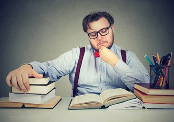 Smart man reading plenty of books