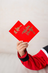 kid holding red pockets shaped like a heart the Chinese means everything is as wishes