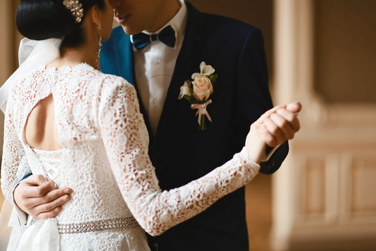 bride and groom in a lace dress and a costume with a butterfly with a budoner with beige and white flowers, in dance