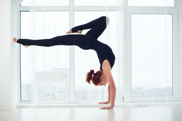 Beautiful sporty fit yogi woman practices yoga handstand asana Bhuja Vrischikasana - Scorpion handstand pose at the yoga studio.