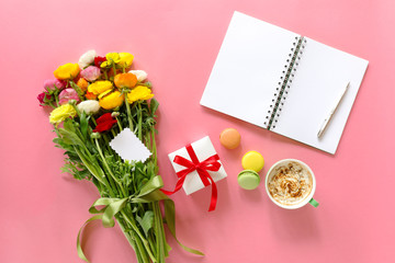 Festive morning concept buttercup flowers bouquet, gift box, cup of cappuccino, makarons cake, clean notebook, pen on the pink background.