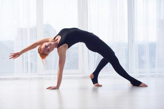 Beautiful sporty fit yogini woman practices yoga asana Camatkarasana - Wild Thing Pose in the yoga studio.