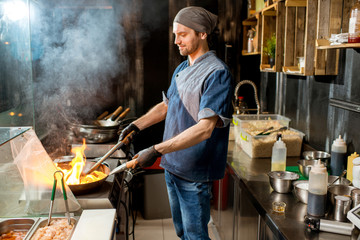 Caucasian chief cook cooking with wok pan on the asian restaurant kitchen