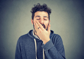 Yawning young man covering mouth