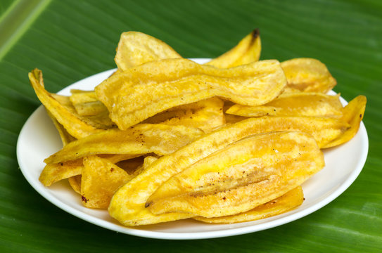 Fried banana chips on white plate with banana leaf background.
