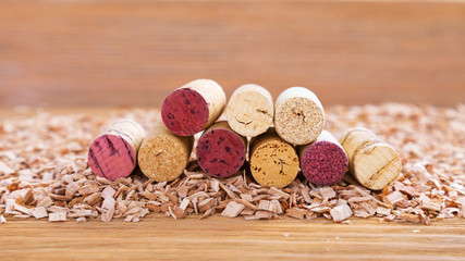 Corks with red stain  lie in a stack on background from wood chips. Natural wood fon with heap of corks from red and white wine. Selective focus. Copy space.
