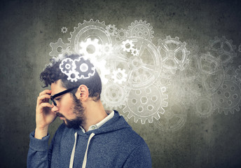 Thoughtful man looking for a solution with gear mechanisms over his head