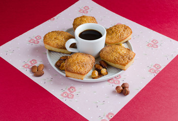 Cakes with caramelized sugar and almond on white plate with cup of coffee on red background