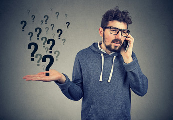 Upset man talking on mobile phone has many questions