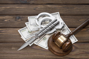 banknotes of dollars. knife, handcuffs, judge's hammer on a wooden background. a crime. arrest. crime.