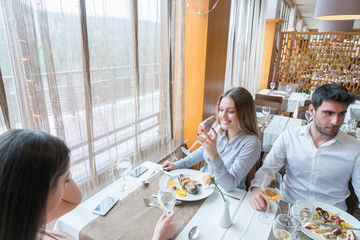 A couple with a female friend having conversation in a restaurant while having launch and glass of champagne.