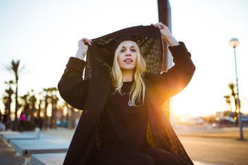Stylish woman putting on warm jacket