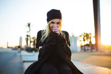 Stylish woman sitting on fence