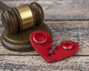 Wedding rings on the figure of a broken red heart, gavel, hammer of a judge on a wooden background. Divorce proceedings, the dissolution of marriage, the division of property.