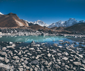 Wall Mural - The boulders on the bottom of Gokyo Lake on the Himalayas background. The Sagarmatha National Park in the north-eastern Nepal. The diversity of the shapes and textures in wild virgin nature.