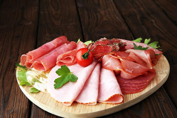 Food tray with delicious salami, pieces of sliced ham, sausage, tomatoes, salad and vegetable - Meat platter with selection