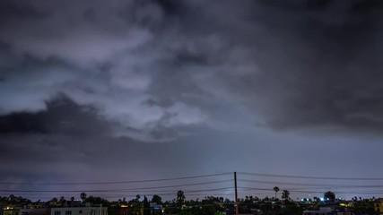Fotobehang - Storm clouds lightning strike bolt over night city of Los Angeles cityscape. 4K