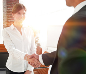woman Manager welcomes the client with a handshake.