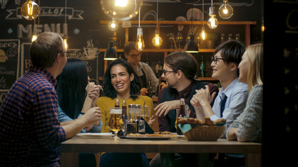 Diverse Group of Young People Have Fun in Bar, Talking, Telling Stories and Jokes. They Drink Various Drinks. They're in the Stylish Hipster Establishment.