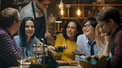In the Bar Waiter Holds Credit Card Payment Machine and Beautiful Woman Pays for Her Order with Contactless Mobile Phone Payments System. She Has Good Time with Her Friends.