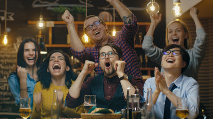 Diverse Group of Friends Watches TV in the Sporstbar. Beautiful Young People Drink, Have Fun and Cheer for their Team.