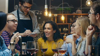 In the Bar/ Restaurant Waiter Takes Order From a Diverse Group of Friends. Beautiful People Drink Wine and Have Good Time in this Stylish Place.