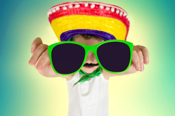 Funny boy in sunglasses  and in Mexican sombrero.
