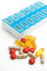Isolated Multiple Vitamins and Medications with Weekly Container on White