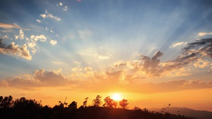 Fotobehang - Beautiful scenic sunset with rays of sun shining through clouds 4K UHD Timelapse