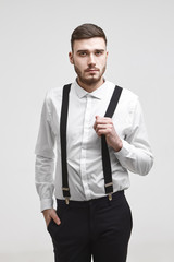 Attractive young bearded corporate worker wearing black trousers and white shirt posing isolated, holding hand in pocket, looking at camera with serious expression, pulling one strap of his suspenders
