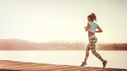 Athletic woman running outdoors by the water