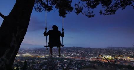 Fotobehang - Man swinging on swings at night on top of mountain overlooking city Los Angeles