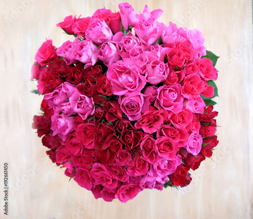 An overhead view of a bunch of 80 pink roses in a circular shape a ...