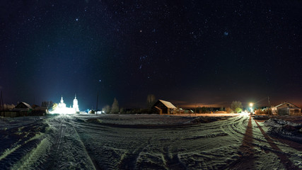 The road in the Russian village. Frosty, winter night. Much snow. Many stars in the sky and the constellation of Orion. The Orthodox Church is illuminated in the distance.